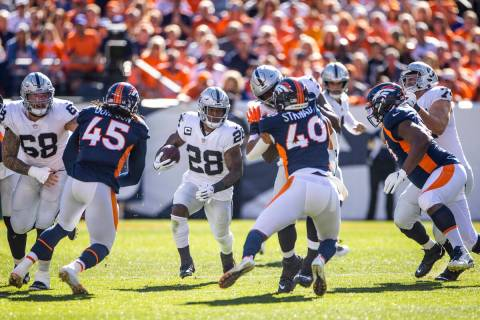 Raiders running back Josh Jacobs (28) looks to a hole in the offensive line versus the Denver B ...