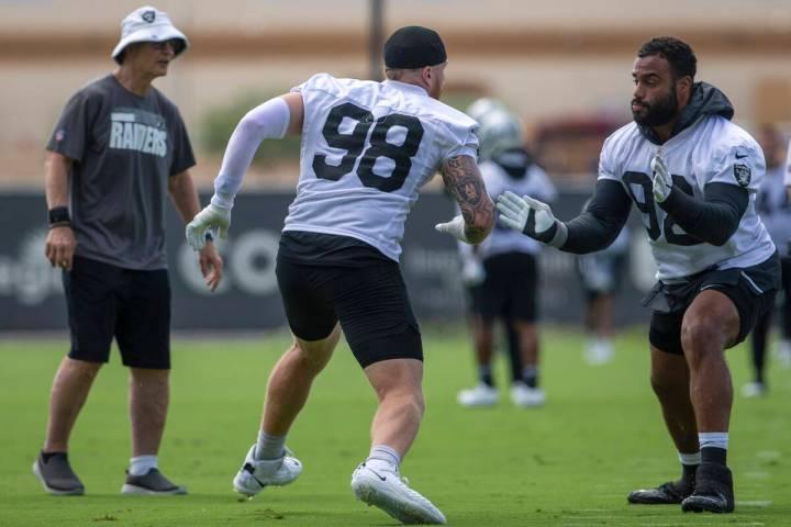 Raiders defensive line coach Rod Marinelli looks on as Raiders defensive ends Maxx Crosby (98) ...