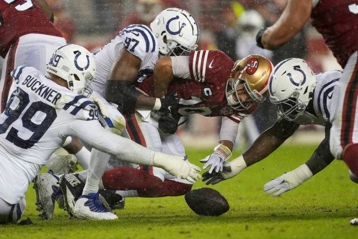 San Francisco 49ers quarterback Jimmy Garoppolo, middle, loses a fumble between Indianapolis Co ...