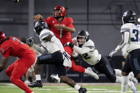 UNLV Rebels quarterback Cameron Friel (7) just gets the ball away with pressure from Utah State ...